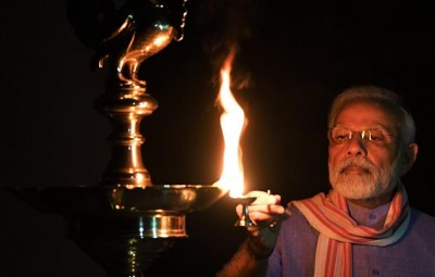 New Delhi: Prime Minister Narendra Modi lights diyas at his residence after he urged people in a video message to the nation to turn off their lights for nine minutes at 09:00 pm on April 5 and light a candle or a 'diya' or even use the flashlight to mark the country' fight against COVID-19 pandemic in New Delhi on April 5, 2020. (Photo: IANS)
